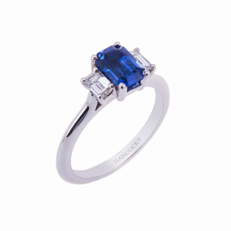 1.20ct sapphire ring set with emerald cut diamonds in a platinum claw setting with tapered shank
