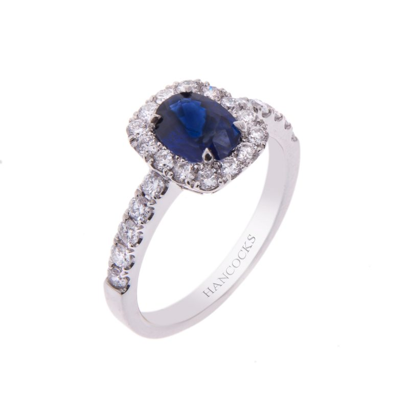 oval sapphire and brilliant cut diamond cluster ring in a platinum claw setting