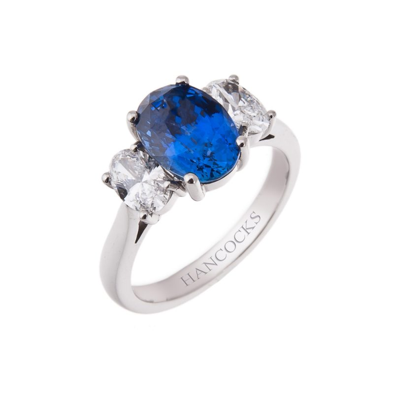 oval three stone ring set with a central sapphire and 2 diamonds