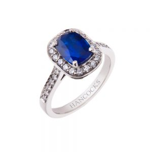 platinum halo set ring mounted with a cushion cut sapphire and brilliant cut diamonds