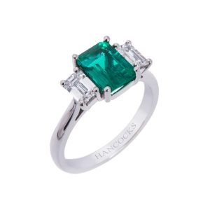 platinum claw set emerald and diamond three stone ring