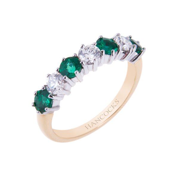 brilliant cut diamond and emerald claw set half eternity ring in 18ct gold