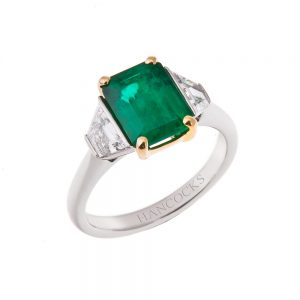 platinum three stone ring set with a central emerald and 2 trapeze cut diamonds