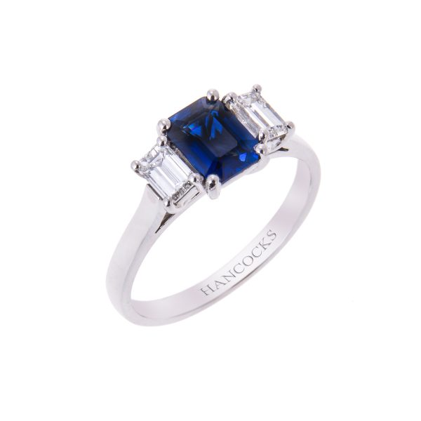 emerald cut sapphire and diamond three stone ring in a platinum claw setting