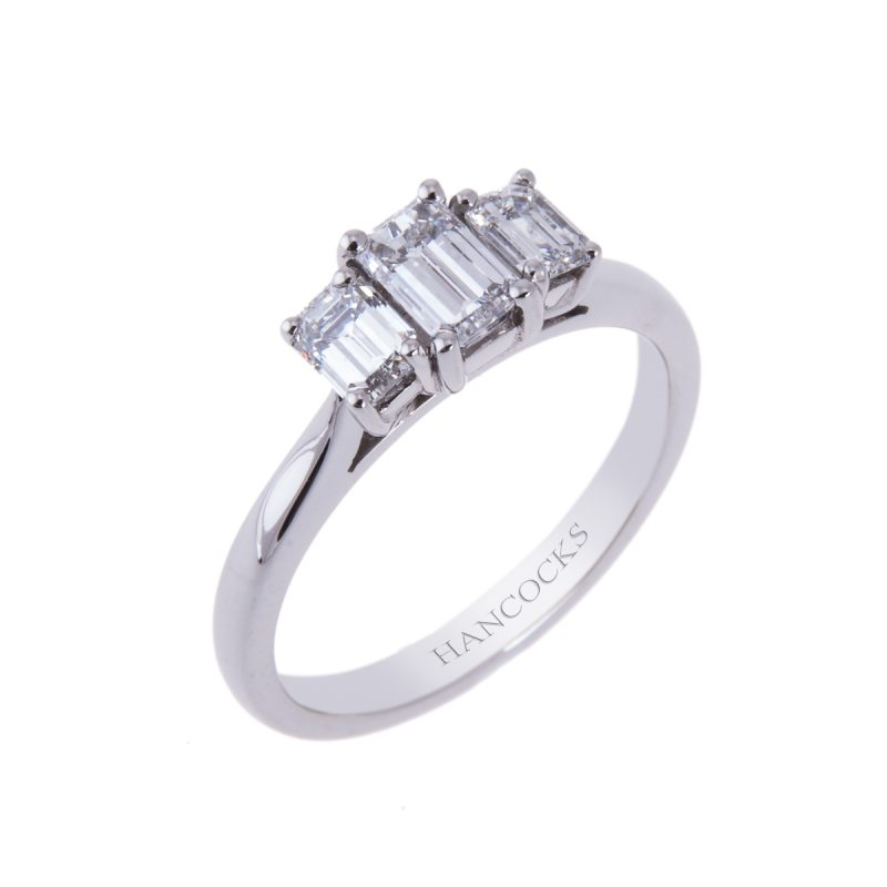 platinum emerald cut diamond trilogy ring mounted in a claw setting