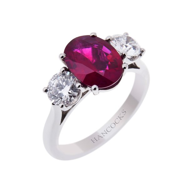 oval ruby and diamond ring set in a platinum 4-claw setting