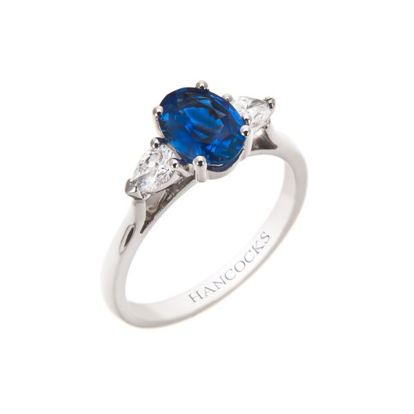 sapphire and pear cut diamond three stone ring in a platinum claw setting