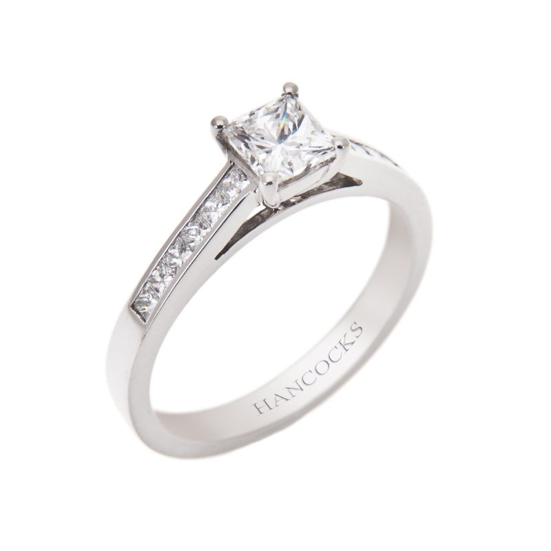princess cut diamond solitaire ring with channel set diamond shoulders in platinum
