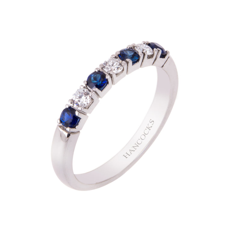 sapphire and diamond half eternity ring in a platinum claw setting