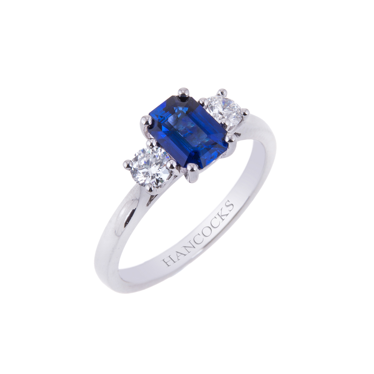 emerald cut sapphire with brilliant cut diamond mounted as a three stone platinum ring